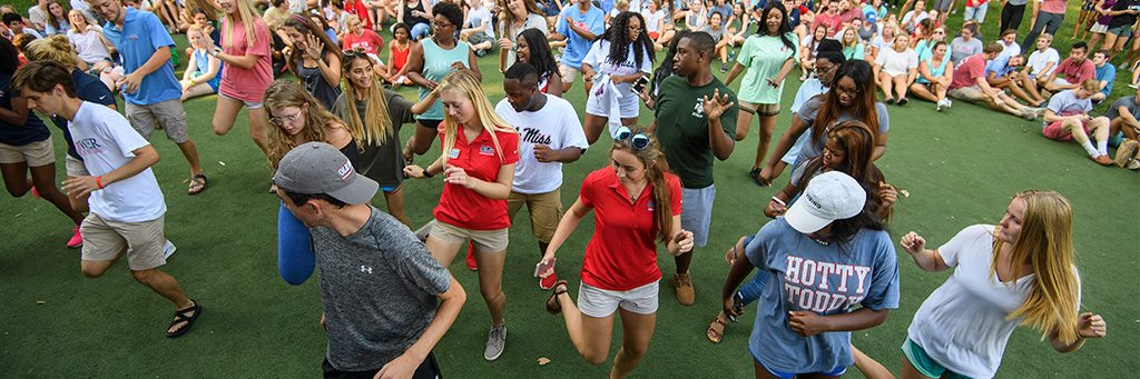 A large group of students dance together in the Grove.